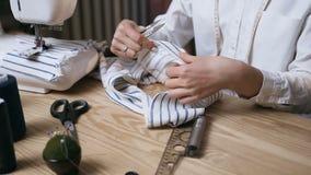 Vrouwelijke handen die met een doek in de fabriek werken stock videobeelden