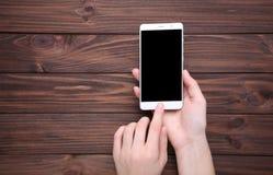 Vrouwelijke handen die mobiele telefoon met het lege scherm op bruine houten achtergrond houden Smartphone op Houten Lijst royalty-vrije stock foto's