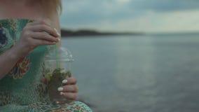 Vrouwelijke handen die mojitococktail op het strand houden stock video
