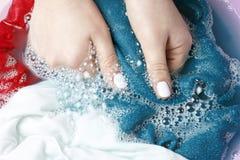 Vrouwelijke handen die multicolored kleren in bassin, hoogste mening wassen royalty-vrije stock fotografie