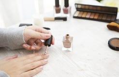 Vrouwelijke handen die nagellak op lijst met cosmetischee producten toepassen Stock Afbeelding