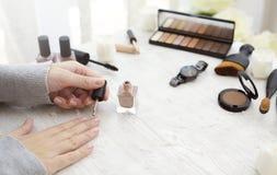 Vrouwelijke handen die nagellak op lijst met cosmetischee producten toepassen Stock Foto
