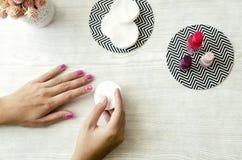 Vrouwelijke handen die nagellak van spijkers op houten lijst opstijgen Royalty-vrije Stock Foto's