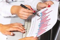 Vrouwelijke handen die onderzoek naar tablet doen, op commerciële vergadering Royalty-vrije Stock Foto's