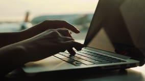 Vrouwelijke handen die op een laptop toetsenbord typen Tegen het venster in de terminal van de luchthaven stock videobeelden
