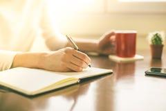 Vrouwelijke handen die op notitieboekje schrijven Stock Fotografie