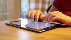 Vrouwelijke handen die op tablet in een koffie texting stock videobeelden