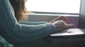 Vrouwelijke handen die op toetsenbord van laptop aan de gang typen Vrouw die met vrienden tijdens het reizen op spoorweg babbelen stock videobeelden