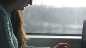 Vrouwelijke handen die op toetsenbord van laptop aan de gang typen Vrouw die met vrienden tijdens het reizen op spoorweg babbelen stock footage