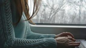 Vrouwelijke handen die op toetsenbord van laptop aan de gang typen Vrouw die met vrienden tijdens het reizen op spoorweg babbelen stock video