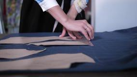 Vrouwelijke handen die patroon op doek in workshop vinden stock footage