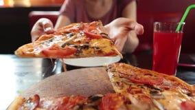 Vrouwelijke handen die plak van pizza met super het uitrekken zich kaas in een koffie nemen Langzame Motie stock video
