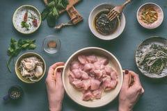 Vrouwelijke handen die pot met kippenborst houden op de achtergrond van de keukenlijst met kommeningrediënten, hoogste mening Royalty-vrije Stock Foto