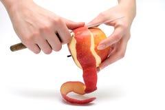 Vrouwelijke handen die rode appel pellen Stock Afbeeldingen