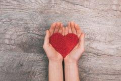 Vrouwelijke handen die rood document hart, op houten achtergrond tonen stock afbeelding