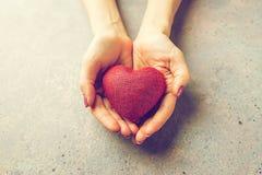 Vrouwelijke handen die rood hart geven Stock Afbeeldingen