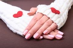 Vrouwelijke handen die rood die hart geven, op gouden achtergrond wordt geïsoleerd Royalty-vrije Stock Afbeelding