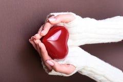 Vrouwelijke handen die rood hart, op gouden achtergrond, de liefde van de Kerstmiswinter geven Stock Fotografie