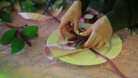 Vrouwelijke handen die servetten vouwen kelner die servet artistiek met vouwen bloemen bij restaurantlijst stock videobeelden