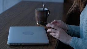 Vrouwelijke handen die smartphone in koffiewinkel houden met laptop op de achtergrond stock videobeelden