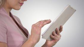 Vrouwelijke handen die tablet op gradiëntachtergrond gebruiken stock footage