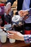 Vrouwelijke handen die thee van een theepot gieten in kop royalty-vrije stock afbeelding
