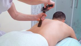 Vrouwelijke handen die tok sen-massage met Thaise hamer op rug van mannelijke patiënt doen stock footage