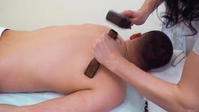 Vrouwelijke handen die tok sen-massage op mannelijke schouders met Thaise hamer doen stock video