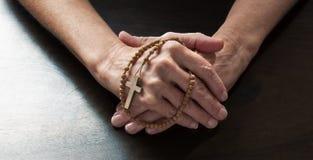 Vrouwelijke handen die vast een Christelijk kruis houden Royalty-vrije Stock Fotografie