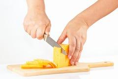 Vrouwelijke handen gesneden kaas op een scherpe raad Stock Afbeeldingen