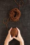 Vrouwelijke handen met bruin garen royalty-vrije stock fotografie