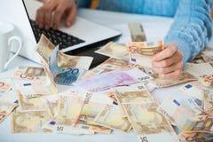 Vrouwelijke handen met contant geld dichtbij laptop royalty-vrije stock foto