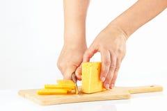 Vrouwelijke handen met een mes gesneden kaas op een scherpe raadsclose-up Stock Foto's