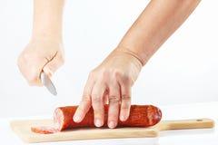 Vrouwelijke handen met een mes gesneden salami op een scherpe raad Royalty-vrije Stock Afbeeldingen