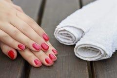 Vrouwelijke handen met een rode manicure en witte handdoeken op houten royalty-vrije stock afbeelding