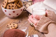 Vrouwelijke handen met hete drank en chocoladekoekjes Stock Afbeelding
