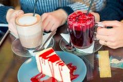 Vrouwelijke handen met hete dranken en zoet dessert royalty-vrije stock foto
