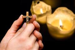Vrouwelijke handen met houten kruis op kaarsenachtergrond stock afbeeldingen