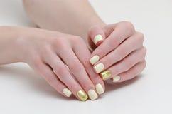 Vrouwelijke handen met manicure, geel met het gouden behandelen van spijkers Witte achtergrond stock afbeelding