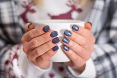 Vrouwelijke handen met marineblauwe de holdingskop thee van de manicurekleur stock afbeeldingen
