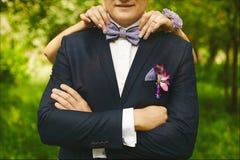 Vrouwelijke handen met modieuze manicure die in bowtie op de hals van een jonge knappe mens in een huwelijkskostuum aanpassen royalty-vrije stock fotografie