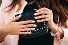 Vrouwelijke handen met mooi nagellak en ringen die kleine zwarte zak houden stock foto
