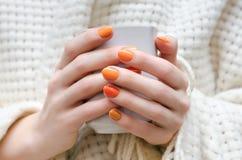 Vrouwelijke handen met oranje spijkerontwerp royalty-vrije stock afbeelding