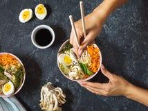 Vrouwelijke handen Miso de Aziatische noedels van Ramen in kommen op donkere steenachtergrond stock foto's