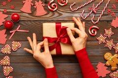 Vrouwelijke handen op Kerstmisgift Stock Foto's