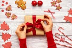 Vrouwelijke handen op Kerstmisgift Stock Afbeelding