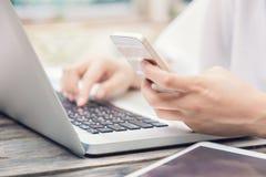 Vrouwelijke handen op laptop toetsenbord en slimme telefoon Royalty-vrije Stock Afbeeldingen