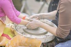 Vrouwelijke handen van pottenbakker en meisjess handen De meester onderwijst student om waterkruik op aardewerkwiel te maken Hoof Royalty-vrije Stock Foto's