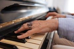 Vrouwelijke handen van rijpe vrouw wat betreft piano stock fotografie
