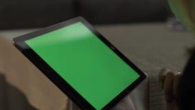 Vrouwelijke handen wat betreft de groene zitting van PC van de het schermtablet bij lijst in koffie stock videobeelden